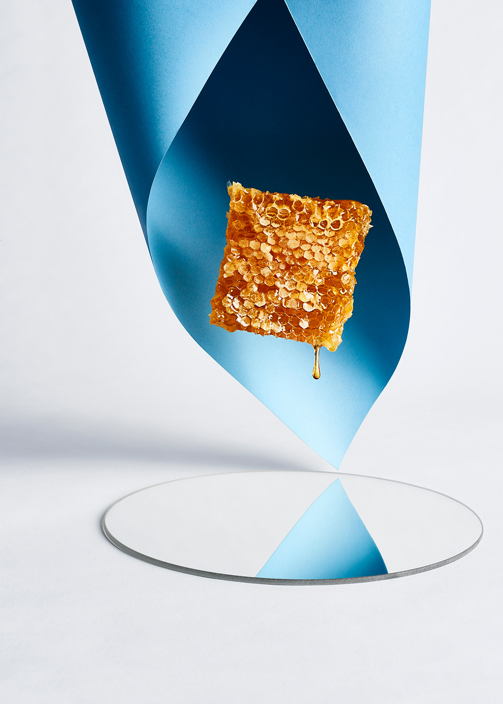 dripping honeycomb conceptual still life shot by camilo mateus